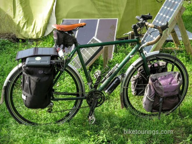 Picture of touring bike with solar panels and gadgets being charged