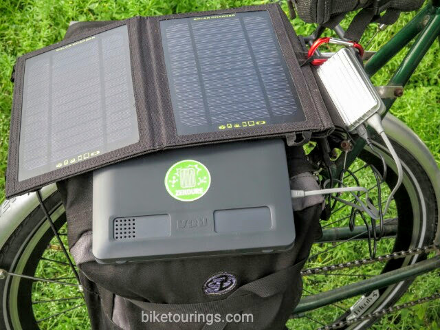 Picture of solar panel with power bank on touring bike while charging tablet